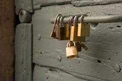 Chiuda su di alcuni lucchetti appesi su una maniglia di vecchia porta Immagine Stock