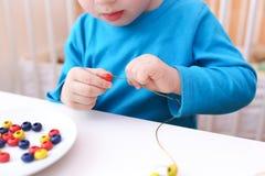 Chiuda su di 2 anni che i ragazzi passa la fabbricazione delle perle Immagini Stock