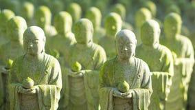Chiuda su di bei molti la statua della pietra del monaco con muschio ed il sole fotografia stock