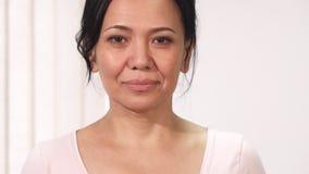 Chiuda su di bella donna asiatica matura con il segno rosa di consapevolezza del cancro al seno del nastro stock footage