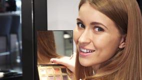 Chiuda su di bella donna che sorride esaminando lo specchio fotografie stock