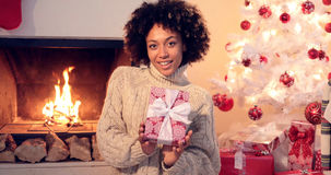 Chiuda su di bella donna di colore che tiene il presente Fotografie Stock