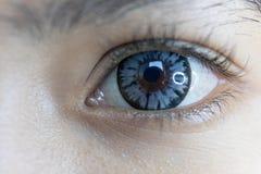 Chiuda su di bella lente di contatto oculare della donna immagine stock