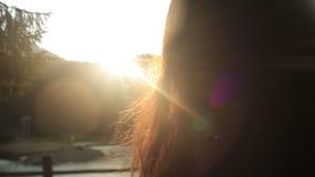Chiuda su di bella ragazza castana con il sole in suoi capelli La giovane crisalide della foresta che sta sul pilastro e gode del archivi video