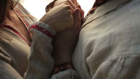 Chiuda su di belle coppie nell'amore in vestiti ucraini tradizionali che si tengono per mano morbidamente sul pilastro sul lago d stock footage