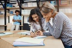 Chiuda su di belle giovani ragazze multi-etniche dello studente di paia che fanno insieme il compito, scrivendo il saggio per la  immagine stock