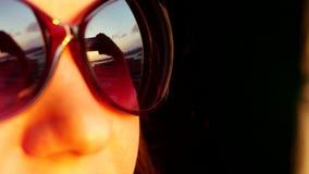 Chiuda su di bello fronte del ` s della donna di vista in occhiali da sole, stando alla finestra e tenere lo smartphone prende l' video d archivio
