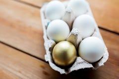 Chiuda su di bianco e delle uova dell'oro in scatola delle uova Fotografia Stock