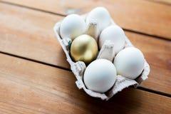 Chiuda su di bianco e delle uova dell'oro in scatola delle uova Fotografie Stock