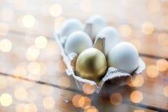 Chiuda su di bianco e delle uova dell'oro in scatola delle uova Immagine Stock Libera da Diritti