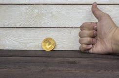Chiuda su di bitcoin dorato e pollice della mostra su su fondo di legno fotografie stock