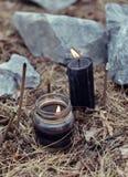 Chiuda su di bruciatura le candele e dei bastoncini d'incenso neri di incenso fra le pietre Immagini Stock Libere da Diritti