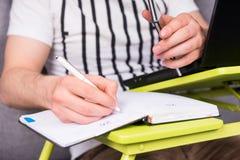 Chiuda su di businessman& x27; scrittura della mano di s Fotografia Stock