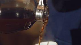 Chiuda su di caffè di versamento nella tazza lentamente archivi video