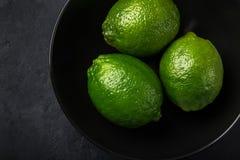 Chiuda su di calce verde fresca in ciotola nera, fondo scuro fotografie stock