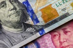 Chiuda su di cento banconote del dollaro sopra una banconota di 100 yuan con il fuoco sui ritratti di Benjamin Franklin e di Mao  Immagine Stock Libera da Diritti