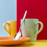 Chiuda su di due gialli e delle tazze blu su una tavola gialla e su un fondo blu e rosso con uno spazio vuoto Fotografia Stock Libera da Diritti
