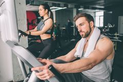 Chiuda su di due giovani che si preparano sulla bici di esercizio Sembrano seri e concentrati sull'allenamento Fotografie Stock Libere da Diritti