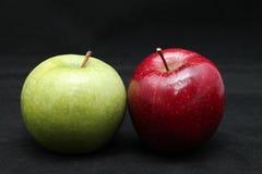 Chiuda su di due mele verdi e rosse brillanti fresche su un fondo del nero scuro Fotografie Stock