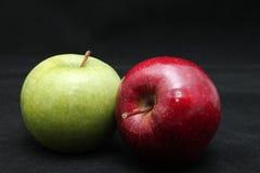 Chiuda su di due mele verdi e rosse brillanti fresche su un fondo del nero scuro Fotografia Stock