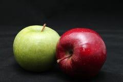 Chiuda su di due mele verdi e rosse brillanti fresche su un fondo del nero scuro Immagine Stock