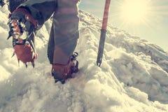 Chiuda su di escursione delle scarpe con i ramponi e la piccozza da ghiaccio Immagine Stock