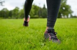 Chiuda su di esercitazione delle gambe della donna su erba in parco Fotografia Stock Libera da Diritti