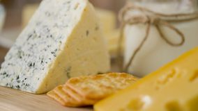Chiuda su di formaggio, dei cracker e del burro sulla tavola stock footage