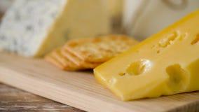 Chiuda su di formaggio e del cracker sul bordo di legno stock footage