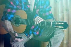 Chiuda su di forti mani dei pantaloni a vita bassa umani che tengono il telefono e la vecchia chitarra Immagine Stock Libera da Diritti