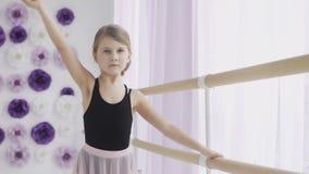 Chiuda su di giovane ballerina che fa gli esercizi vicino alla sbarra di balletto nello studio video d archivio