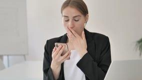 Chiuda su di giovane donna di affari nella scossa facendo uso di Smartphone video d archivio