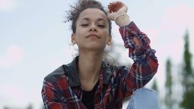Chiuda su di giovane donna afroamericana che sorride ad una macchina fotografica stock footage