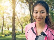 Chiuda su di giovane donna asiatica felice che si scalda il suo corpo allungando il suo corpo prima dell'esercizio di mattina Fotografie Stock