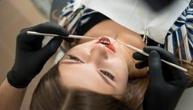 Chiuda su di giovane femmina che ha controllo dentario su in clinica dentaria Dentista denti d'esame del ` una s del paziente con fotografie stock libere da diritti