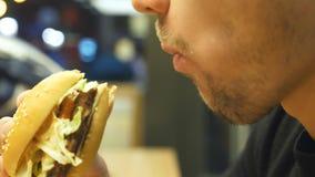 Chiuda su di giovane hamburger o cheeseburger mangiatore di uomini dell'interno alla sera Vista laterale della bocca maschio che  archivi video