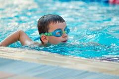 Chiuda su di giovane nuoto del ragazzo nello stagno Fotografia Stock