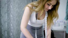 Chiuda su di giovane progettista femminile che sta alla tavola nell'adattamento dello studio che fa le linee sul panno con gesso  archivi video