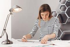 Chiuda su di giovane progettista femminile femminile serio bello con capelli scuri lunghi in vestiti a strisce alla moda lavorand Fotografia Stock