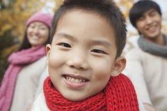 Chiuda su di giovane ragazzo con la famiglia in parco in autunno Fotografie Stock Libere da Diritti