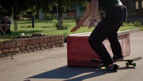 Chiuda su di giovane skateboarder in abbigliamento casual che salta sopra il bordo nel giorno di estate L'adolescente sta avendo  archivi video
