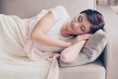 Chiuda su di giovane sonno castana splendido sul beige accogliente Fotografie Stock