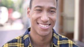 Chiuda su di giovane uomo africano sorridente, all'aperto stock footage