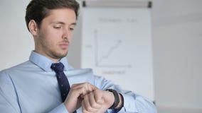 Chiuda su di giovane uomo d'affari Using Smartwatch sul lavoro archivi video