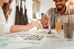 Chiuda su di giovani artisti allegri che riuniscono nello studio immagini stock