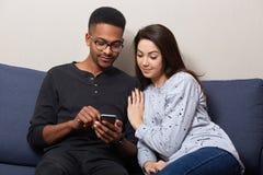 Chiuda su di giovani coppie multiculturali che si siedono sul sofà a casa guardano in schermo dello Smart Phone, facendo uso di I fotografia stock