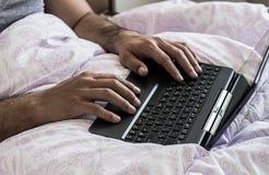 Chiuda su di giovani dita delle mani del maschio che funzionano a letto sul computer portatile che scrive sulla tastiera Immagini Stock Libere da Diritti