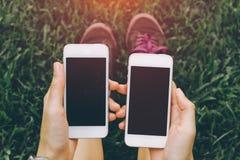 Chiuda su di giovani mani sane asiatiche del ` s delle donne che tengono il telefono delle cellule due con lo spazio in bianco de fotografie stock libere da diritti