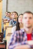 Chiuda su di giovani studenti che si siedono nell'aula Immagine Stock Libera da Diritti