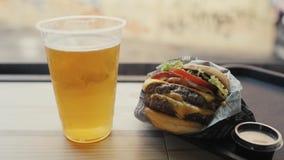 Chiuda su di grandi doppi hamburger, manzo del pomodoro e birra saporiti video d archivio